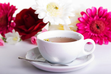 Cup of tea with flower on table