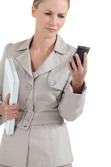 Female executive looking puzzled at her phone