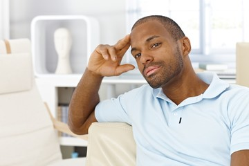 Casual man thinking in living room
