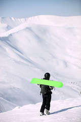 Young snowboarder walking up mountain slope