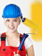Young woman in overall is painting her wall yellow