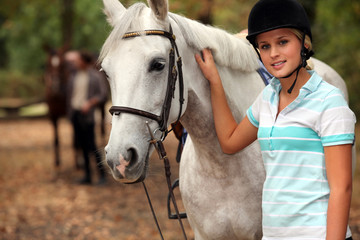 Blond teenager next to horse