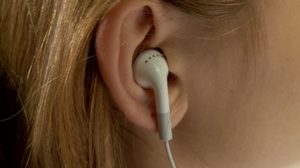 Ear with the earpiece (the Girl listens to music)