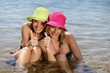 Two female friends at the beach giving the thumbs-up