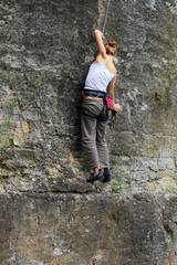 Female rock climber clinging to a cliff on her way up