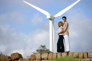 Couple standing before a wind turbine