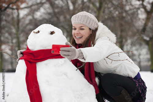 A young woman photographing a snowman