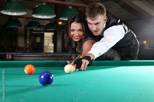 Staande foto Portrait of a couple playing snooker in a dark club