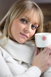 Woman drinking hot beverage to warm herself up