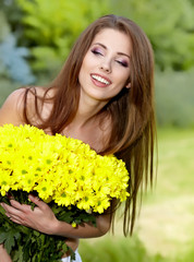 Happy smiling young woman with flower bouquet