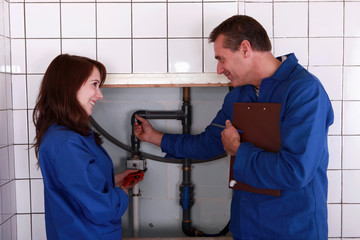 plumber and his apprentice examining the pipes