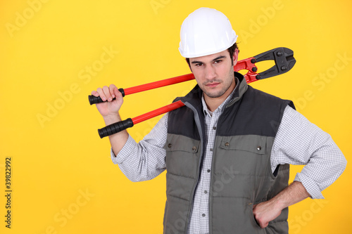 Tradesman carrying a pair of large clippers on his shoulder