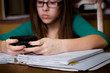 Girl Distracted by Texting on Cell Phone while Doing Homework