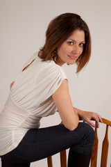 woman in a chair backwards, smiling