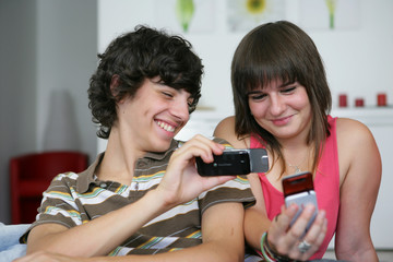 Teens looking at pictures on their mobile phones