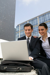 Business couple laughing in front of a laptop outdoors