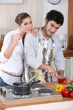 portrait of young man cooking in kitchen with girlfriend
