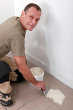 Decorator spreading adhesive on a tiled floor