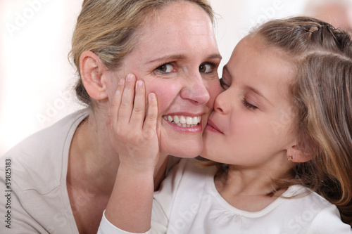 little girl kissing woman