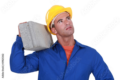 Laborer carrying cinderblock