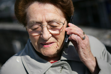 Elderly lady making a call outdoors