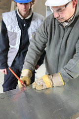 Engineer cutting sheet metal with apprentice
