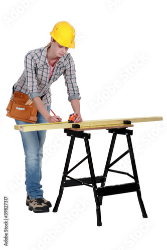 Woman measuring plank of wood