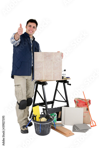 tradesman posing with his tools and building materials