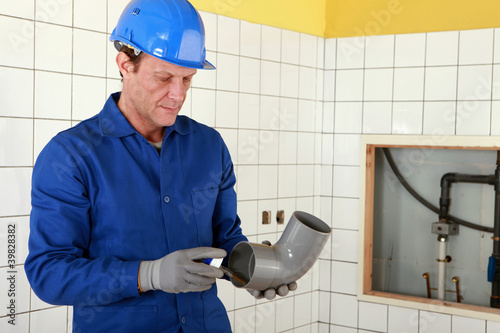 Plumber working on public restroom