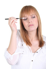 woman putting make-up on her eyes