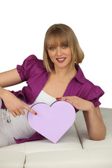 young cheerful blonde on divan with box in shape of heart