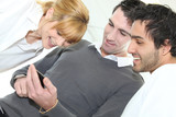 Three people looking at mobile telephone screen