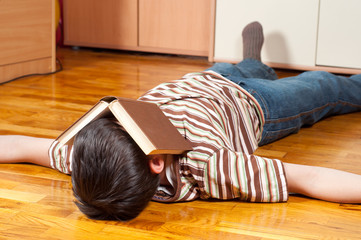 Teenage boy sleeping on the floor with book covering his face