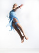 Motion. Young woman in blue dress jumping in studio
