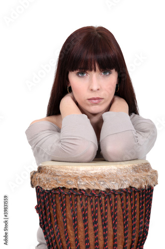 Brunette leaning on bongo drum