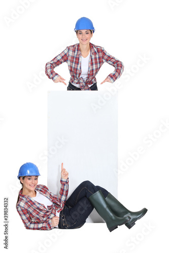 twosome of jovial girls with blue hard hat