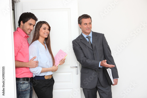 Promoter and young couple visiting a flat