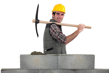 Builder carrying pick-axe stood by wall