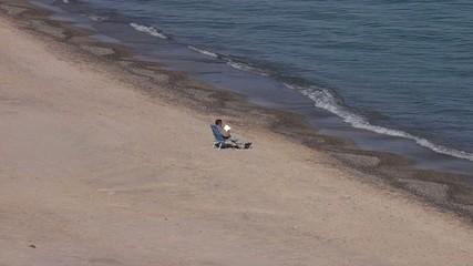 Hombre leyendo en la orilla del mar