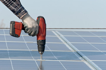 Man with screwdriver working on a photovoltaic plant