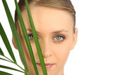Woman hiding behind a fern