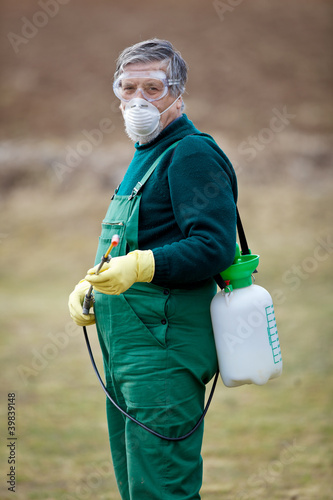gardener applying an insecticide/a fertilizer to his fruit