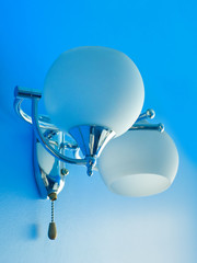 Blue texturized wall with white lamp