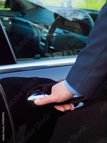 Businessman's hand opening door of his luxury car