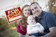 Happy Young Family in Front of Sold Real Estate Sign