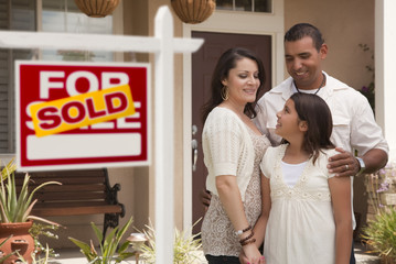 Hispanic Family in Front of Home with Sold Real Estate Sign