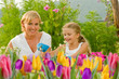 Mother with daughter planting flowers into the flowerpot