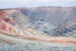 Big mine pit with little dump trucks and reddish soil - 39856956
