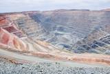 Big mine pit with little dump trucks and reddish soil