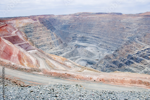 Leinwandbild Motiv Big mine pit with little dump trucks and reddish soil